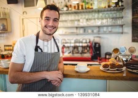 Portrait of happy young male barista at coffee house