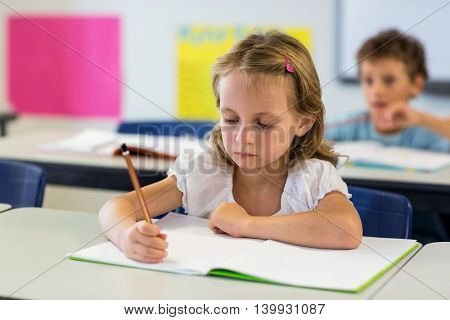 Serious girl writing on book in classroom