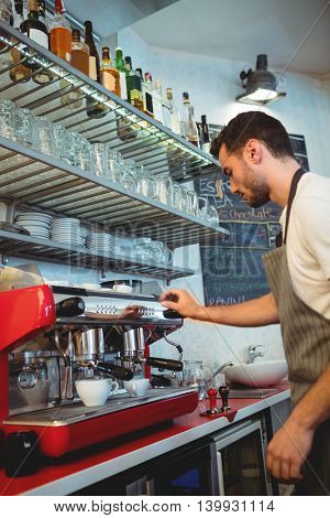 Side view of young waiter using coffee maker at cafe