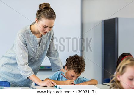 Female teacher looking at student writing on book in classroom