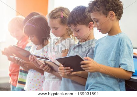 Schoolchildren using digital tablets in classroom