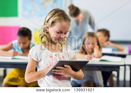 Cute girl using digital tablet in classroom