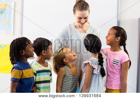 Happy female teacher with schoolchildren in classroom