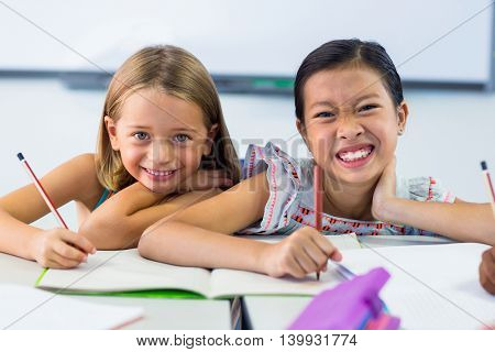 Portrait of smiling schoolgirls writing on books in classroom