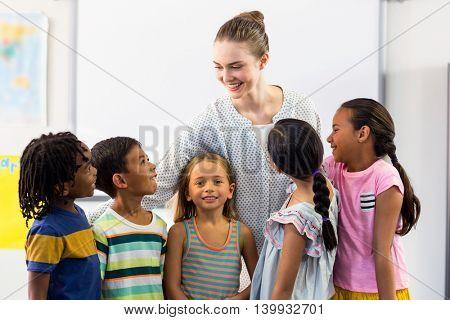 Smiling female teacher with schoolchildren in classroom