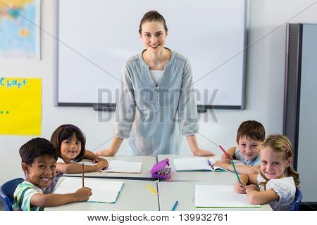 Portrait of happy female teacher with students in classroom