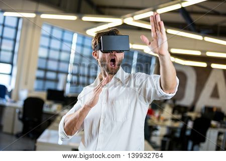 Young businessman gesturing while using virtual reality simulator in office