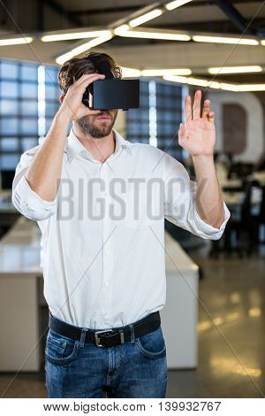 Young businessman using virtual reality simulator in office