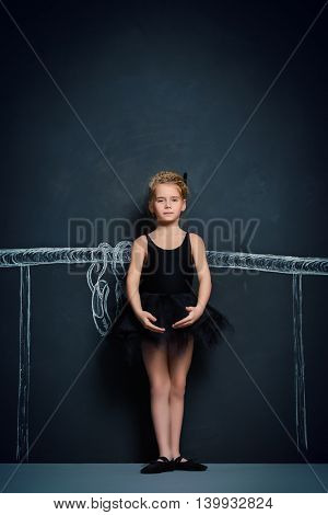 Beautiful girl ballet dancer in black leotard and tutu posing in studio over black background.
