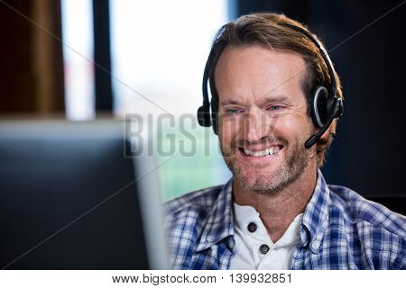 Close-up of smiling creative businessman working on computer in office