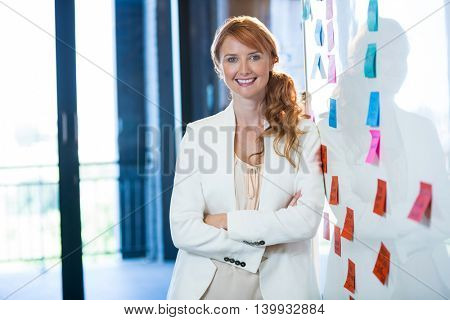 Portrait of pretty smiling businesswoman leaning on whiteboard in creative office
