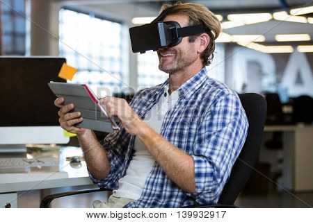 Happy creative businessman using virtual reality simulator in office