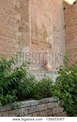 July 17, 2016-Monastery of the Benedictines of Subiaco in the Lazio-Italy-The statue of the Madonna located beneath a fresco of an unidentified author depicting St. Benedict and his vocation
