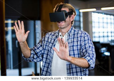 Creative businessman using virtual reality simulator in office