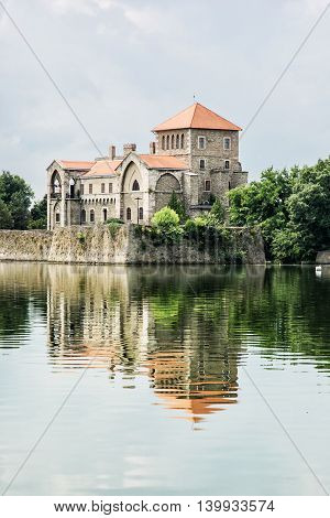 Beautiful castle in Tata Hungary. Travel destination. Architectural theme. Beautiful place. Fortress is reflected in the lake. Vertical composition.