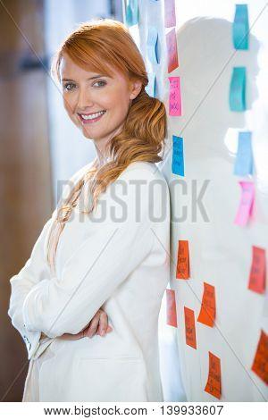 Portrait of pretty businesswoman leaning on whiteboard in office