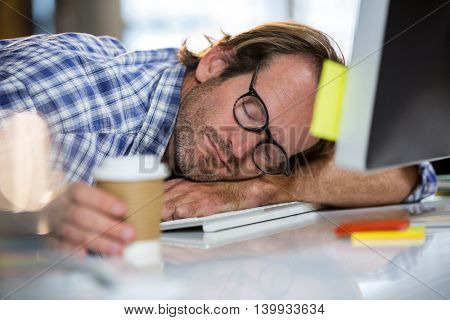 Creative businessman napping on computer desk in office