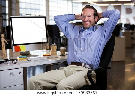 Portrait of businessman sitting with hands behind head by computer desk in office