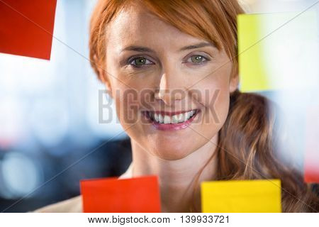 Close-up portrait of pretty businesswoman seen through glass in office
