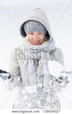 Cute casual young woman playing with snow in winter time.