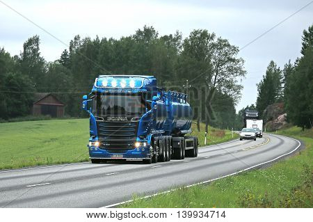TENHOLA, FINLAND - JULY 22, 2016: New blue Scania R580 tank truck for bulk transport on summer highway in South of Finland. The driver flashes the high beam lights briefly.