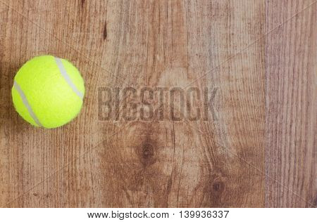 sport, fitness, game, sports equipment and objects concept - close up of tennis ball on wooden floor from top