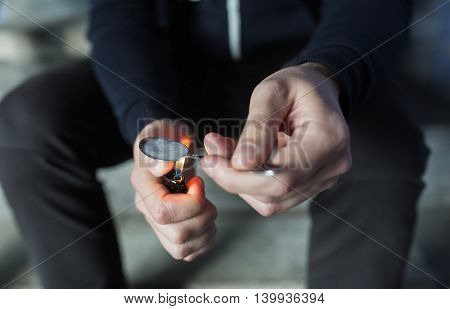 drug use, crime, addiction, substance abuse and people concept - close up of addict with lighter and spoon preparing dose of crack cocaine on street