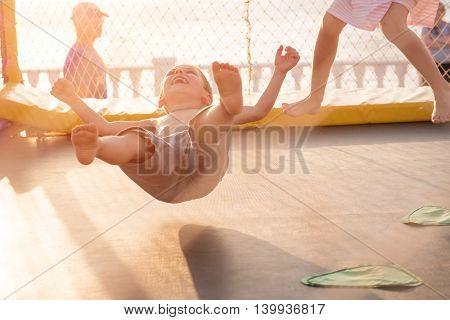 little boy jumping on trampoline on coast