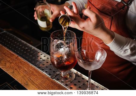 Barman pouring hard spirit into glass in detail. no face