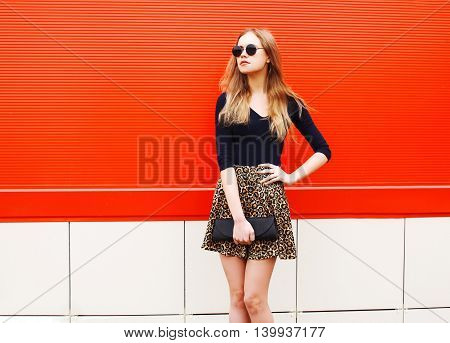 Fashion Beautiful Woman In Leopard Skirt Sunglasses Handbag Clutch Posing Over Colorful Red Backgrou