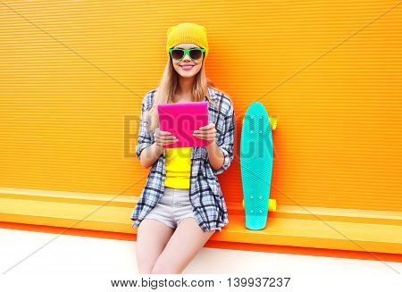 Fashion Cool Girl Using Tablet Pc In City With Skateboard Over Colorful Orange Background