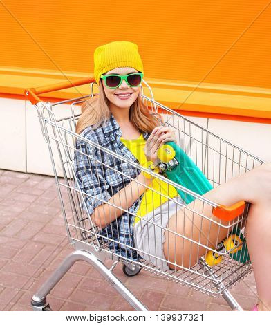 Fashion Pretty Cool Girl In Trolley Cart With Skateboard Over Colorful Orange Background