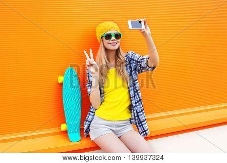 Fashion Pretty Cool Girl Makes Self Portrait On Smartphone Over Colorful Orange Background