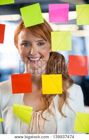 Portrait of smiling businesswoman seen through glass with colorful adhesive notes