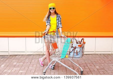 Fashion Pretty Girl With Shopping Trolley Cart And Skateboard Over Colorful Orange Background