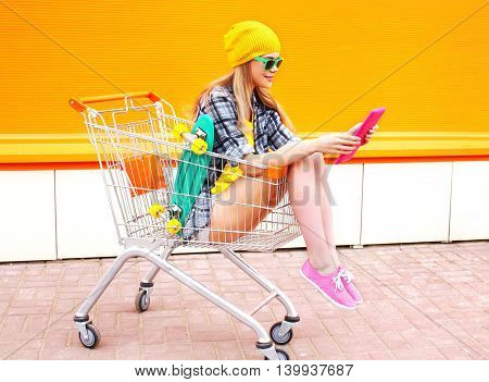 Pretty Cool Girl Using Reading Tablet Pc In Shopping Trolley Cart Over Colorful Orange Background