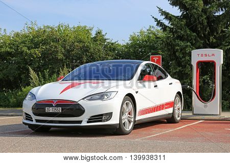 PAIMIO, FINLAND - JULY 24, 2016: White and red unique signage design Tesla Model S charging on Supercharger Station in South of Finland. In 2016 there are 5 Supercharging stations in Finland.