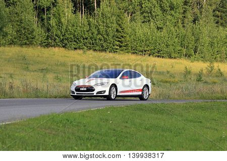 PAIMIO, FINLAND - JULY 24, 2016: Tesla Model S unique design electric car drives along rural road in South of Finland at summer surrounded by green nature.
