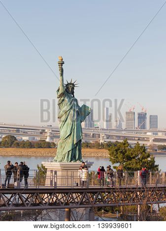 Tokyo - February 3 2015: Tourists around the female figure of Statue of Liberty with torch in the background of the urban landscape of Tokyo Bay in the evening February 3 2015 Tokyo Japan