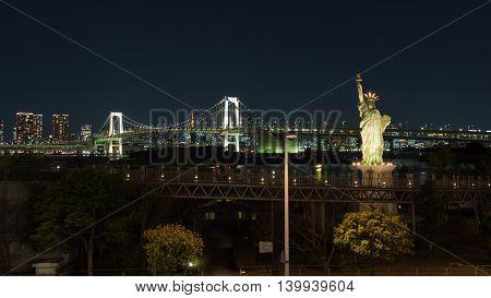 Tokyo - February 3 2015: Rainbow Bridge glows in the dark Tokiyskoy bay and people around the illuminated Statue of Liberty in the evening February 3 2015 Tokyo Japan