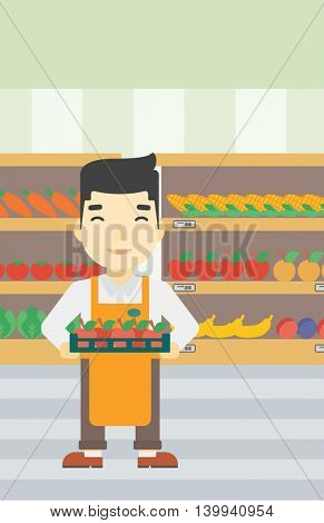An asian young male supermarket worker holding a box with apples on the background of shelves with vegetables and fruits in supermarket. Vector flat design illustration. Vertical layout.