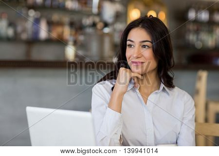 Thoughtful businesswoman sitting on table with laptop in restaurant