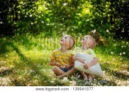 Kids Having Fun With  Pillows Outdoors. Two Children Relax In A