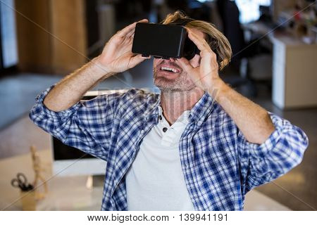 Creative smiling businessman using virtual reality simulator in office