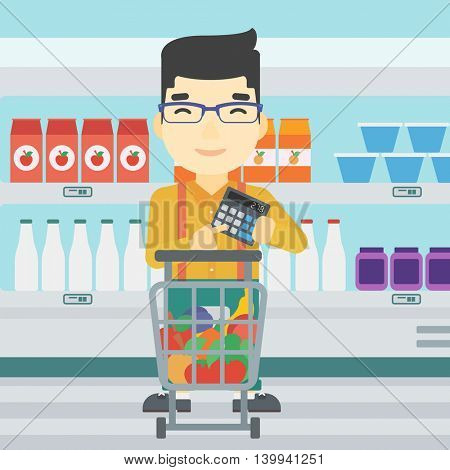 An asian young man at the supermarket with calculator and supermarket trolley full with products. Man checking prices with calculator. Vector flat design illustration. Square layout.