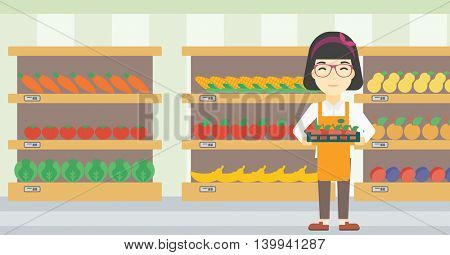 An asian young female supermarket worker holding a box with apples on the background of shelves with vegetables and fruits in supermarket. Vector flat design illustration. Horizontal layout.
