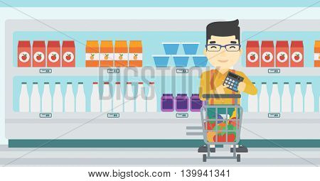 An asian young man at the supermarket with calculator and supermarket trolley full with products. Man checking prices with calculator. Vector flat design illustration. Horizontal layout.