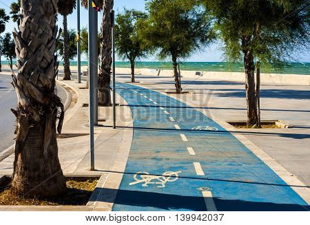 Bike lane sea city. Sign for bicycle painted on the asphalt colored. Car and traffic in background. Dividing line diminishing perspective.