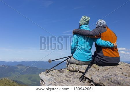 The guy with the girl sitting on a rock in the mountains against the blue sky.