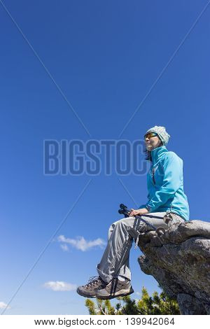 The girl sitting on a rock in the mountains against the blue sky.